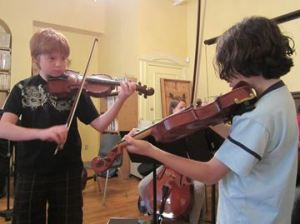 Max and Dylan learned violin through the El Sistema Aeolian program and now help teach the adult orchestra.